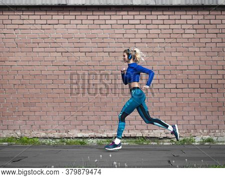 Woman Jogging Outdoor In A Sunny Day. Sport And Healthy Lifestyle Concept. Brick Wall Background.