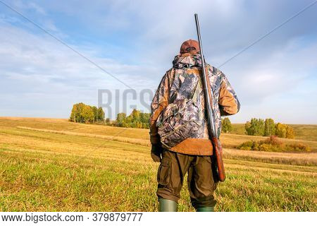 A Hunter With A Hunting Gun And Hunting Form To Hunt In An Autumn Forest Or Field.