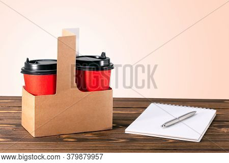 Craft Paper Bag With Coffee Cups  On The Wooden Table With Copy Space. Concept Order Coffee To Go.