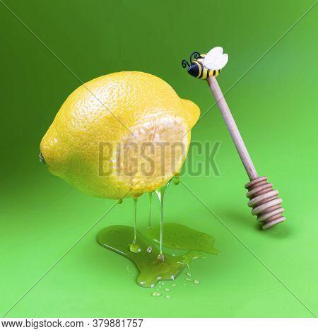 Honey Trickles And Drips From Levitating Lemon. Lemon And Dipper For Honey On Green Background. Unre