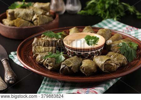Stuffed Grape Leaves - Traditional Mediterranean Cuisine, Dolma On A Brown Plate With Fresh Parsley