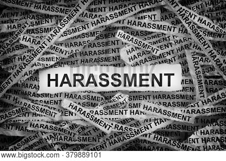 Harassment. Torn Pieces Of Paper With The Word Harassment. Concept Image. Black And White. Close Up.
