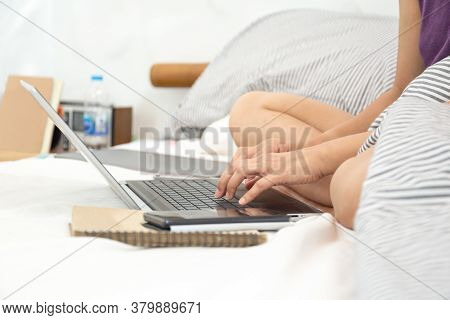 Womans Sitting On Bed In Bedroom Working With Computer.