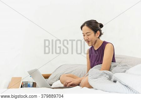 Happy Smiling Woman Working On A Laptop Sitting On The Bed.