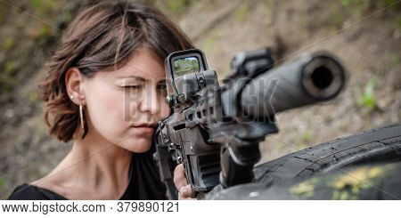 Beautiful And Attractive Woman Soldier Shooting With Rifle Machine Gun From Behind And Around Cover