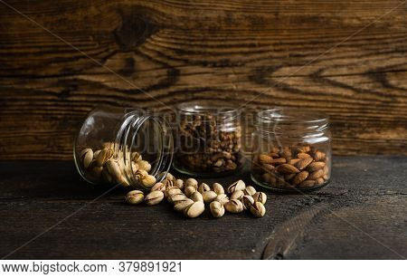 Pistachios Scattered On The Vintage Table From A Jar. Pistachio Is A Healthy Vegetarian Protein Nutr