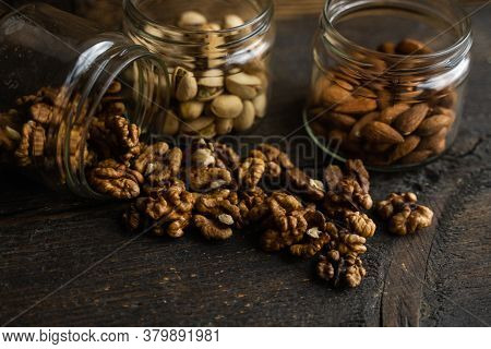 Walnut Scattered On The Wooden Vintage Table From A Jar. Walnut Is A Healthy Vegetarian Protein Nutr