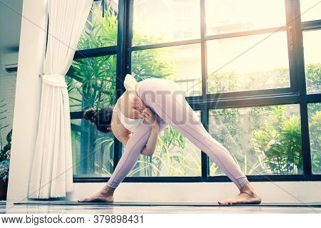 Women Who Exercise Yoga In The White Living Room At Home. Yoga And Meditation Concepts Have Health B