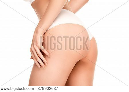View Of Young Woman In Panties Standing And Touching Leg Isolated On White