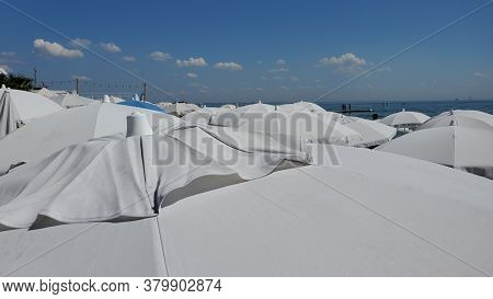 Tops Of Many White Beach Umbrellas Near Coastline With High Blue Sky And Small White Clouds. Textile