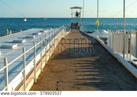 Pier With A Lifeguard Booth On The Background Of The Sea At Sunset