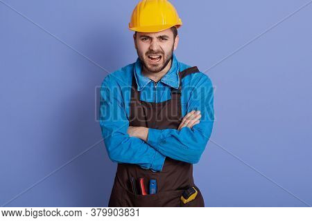 Annoyed Emotional Workman Wearing Yellow Protective Construction Helmet, Shirt And Brown Apron, Has