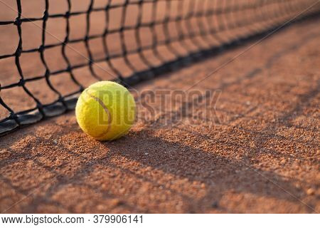 Tennis Ball On The Court. Sports Equipment For Active Lifestyle. Ball And Court As A Background.