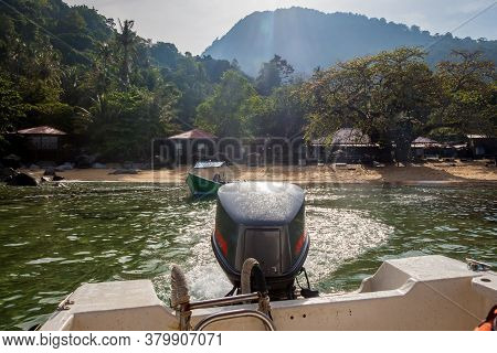 The Stern And Outboard Motor Of A Boat Leaving A Tropical Island In Morning, Tiomen Island, Malaysia