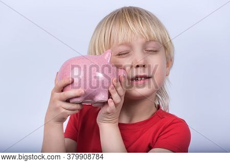 Blond Boy Holding His Piggy Bank. Portrait Of Child With Piggy Bank On White Background