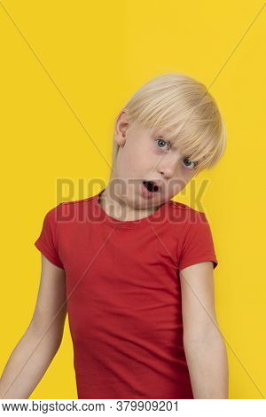 Surprised Fair-haired Boy In Red Shirt Looking At Camera. Portrait Of Child On Yellow Background.