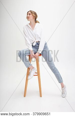 Portrait Of Young Pensive Caucasian Woman Posing In Shirt And Blue Jeans, Sitting On Stool In White
