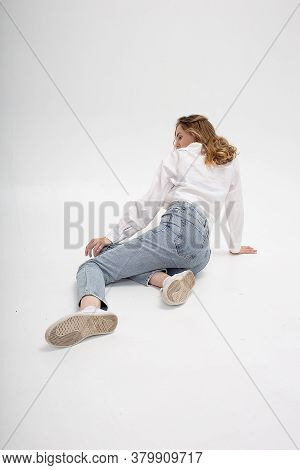 Portrait Of Young Pensive Caucasian Woman Posing In Shirt And Blue Jeans, Sitting On White Studio Fl