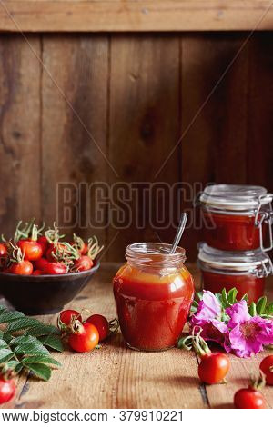 A jar of rose hip jelly and fresh rose hips on wooden table.