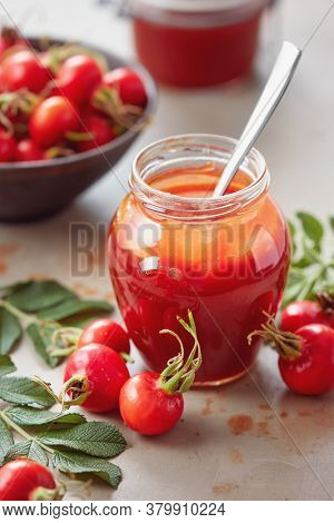 A jar of rose hip jelly and fresh rose hips on  table.