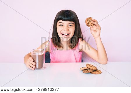 Young little girl with bang sitting on the table having breakfast smiling and laughing hard out loud because funny crazy joke.