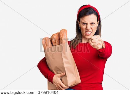 Young beautiful woman holding paper bag with bread annoyed and frustrated shouting with anger, yelling crazy with anger and hand raised