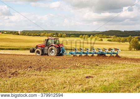 Plow The Land. Farmer In Red Tractor Preparing Land With Plow For Sowing