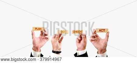 Plan Do Check Act. Hands Hold Wooden Blocks With Plan Do Check Act Inscriptions On White Background.