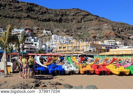 Gran Canaria, Spain - December 2, 2015: People Rent Colorful Paddle Boats At Puerto Mogan Beach In G