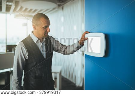 A Mature Handsome Caucasian Man Entrepreneur Using A Multifunctional Wall-mounted Terminal Panel Wit