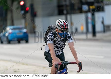 London, England - May 27, 2020: Young Adult Man Riding On A Bicyle In A Commuter Cycle Lane Along Th