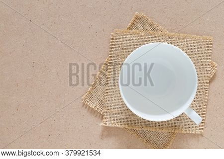 Empty White Ceramic Cup Of Coffee Was Placed On Burlap Cloth On Craft Board.