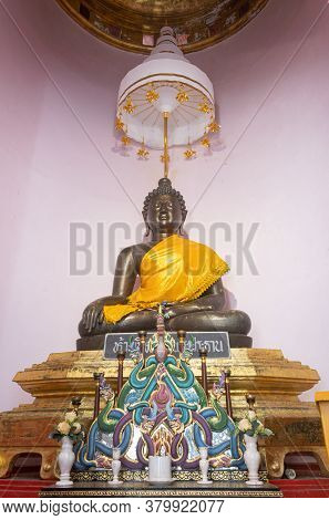 Phayao, Thailand - Dec 8, 2019: Metal Buddha Statue On Base And Sacrifice In Pagoda Or Stupa In Anal
