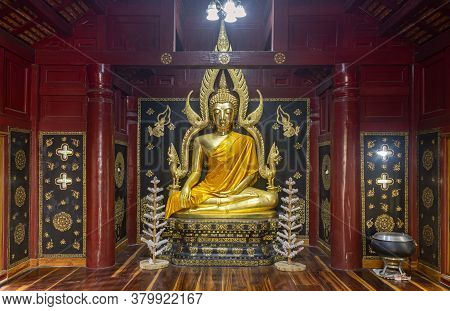 Phayao, Thailand - Dec 8, 2019: Gold Buddha Statue In Wood Pagoda Or Stupa With White Light From Bul