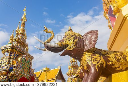 Phayao, Thailand - Dec 31, 2019: Brown Elephant Statue And Gold Pagoda Or Stupa On Blue Sky Backgrou