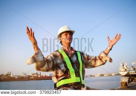 The Male Engineer Worked At The Pier, Wearing A White Hat, Raising Both Hands, Strong And Powerful T