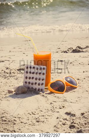 Medical Pills, Carrot Juice And Sunglasses On Sand At Beach, Concept Of Prevention Of Vitamin A Defi