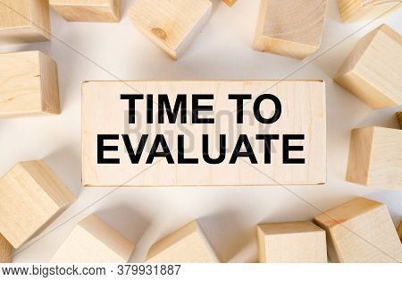 Time To Evaluate. Text On Wood Board Near Wood Cubes