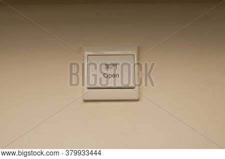 White Plastic Light Electric Switch In English And Chinese On White Plain Wall