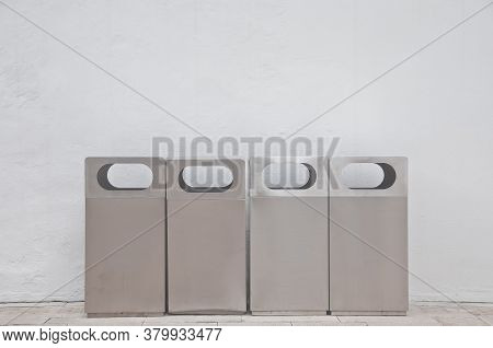 Four Of Different Types Of Grey Metal Bins Lays In Front Of White Building Wall