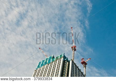 Underconstruction Building In Progress With Many Construction Cranes And Bright Sunny Blue Sky With