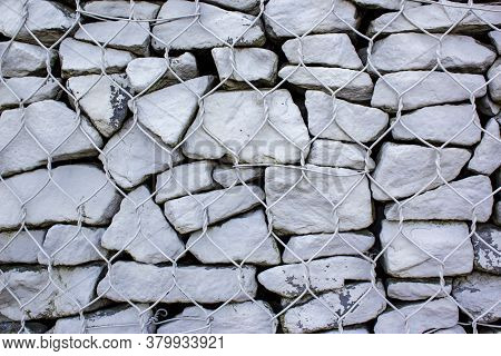Gabion Made Of White Stone And Metal Wire Mesh. A Stone Wall That Uses Metal And Stone In Harmony. E