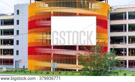 White Poster Mockup Hangs On Red Orange Construction Coverage Near Green Flowerbed In City Centre On