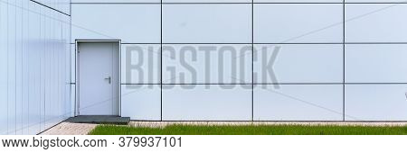 Local City Building Wall Of White Colour With Grey Door And Stairs At Panoramic Windows And Green Gr