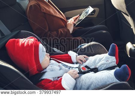 Mother With Her Small Child In A Baby Car Seat Ride In The Back Seat Of A Taxi