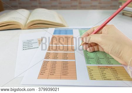 Hand Holding Pencil Over English Grammar Sheet On Table In Classroom
