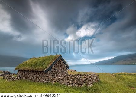 Small House Near A Blue Lake, A Small House Made Of Stones With Covered Grass On The Shore Of A Beau