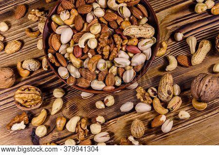 Various Nuts (almond, Cashew, Hazelnut, Pistachio, Walnut) In Ceramic Plate On Wooden Table. Vegetar