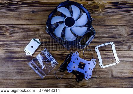 Modern Cpu Cooler With Heat Pipes And Installation Kit On Wooden Background