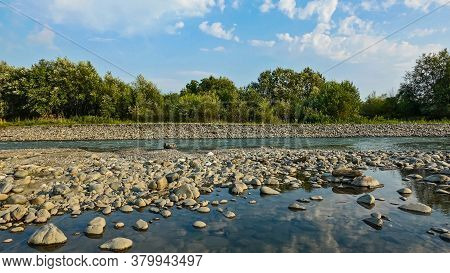 Mountain River In Summer. The Riverbed Is Partially Dry. Between The Pebbles There Is A Lake Of Wate